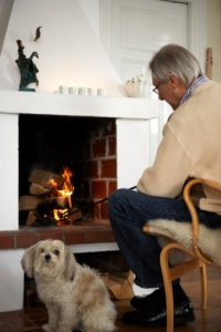 75252929-senior-man-with-dog-sitting-near-fireplace-gettyimages